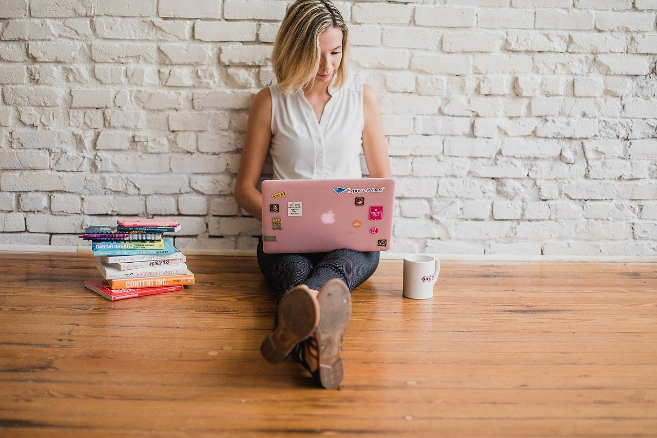 Cover Image - A writer writing on her laptop with books beside her.