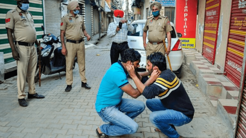 Policemen force two men to do sit ups for flouting the lockdown rules, at Dharampura Bazar in Patiala on 24 March 2020 | PTI
